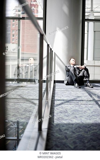 Low view looking at a Caucasian businessman taking a break sitting at the base of a column in a convention centre space