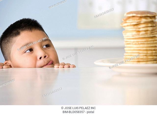 Hispanic boy licking lips at stack of pancakes