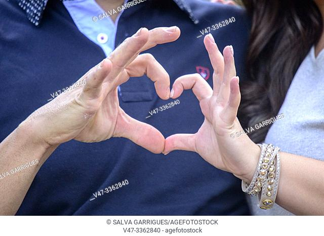 wedding couple make a heart by linking their fingers