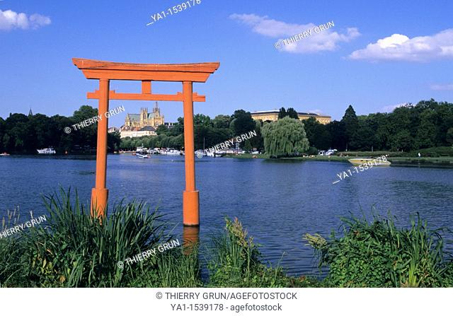 Japanese torii gate on city lake (plan d'eau du Saulcy) with on background cathedral Saint Etienne, Metz town, Moselle, Lorraine region, France, Europe