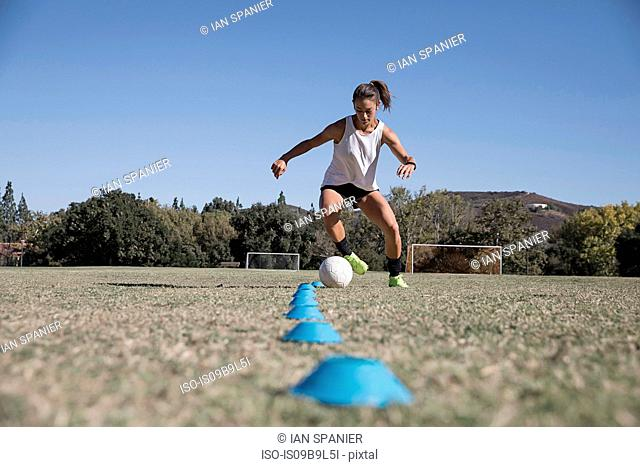 Woman dribbling football