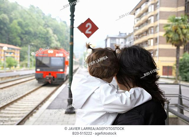 Mother (35 years old) and daughter (2 years old) waiting for the tramway. Railway station