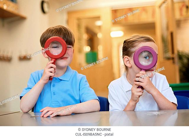 Schoolboy and girl looking through magnifying glasses in classroom at primary school, portrait