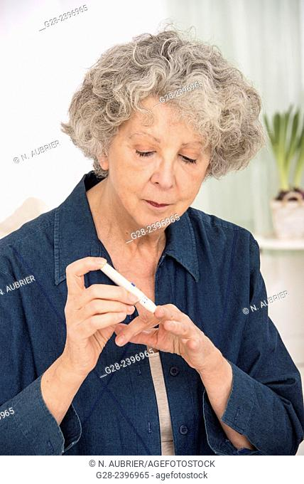 Beautiful senior woman using an auto blood tester for diabetes on one of her finger at home