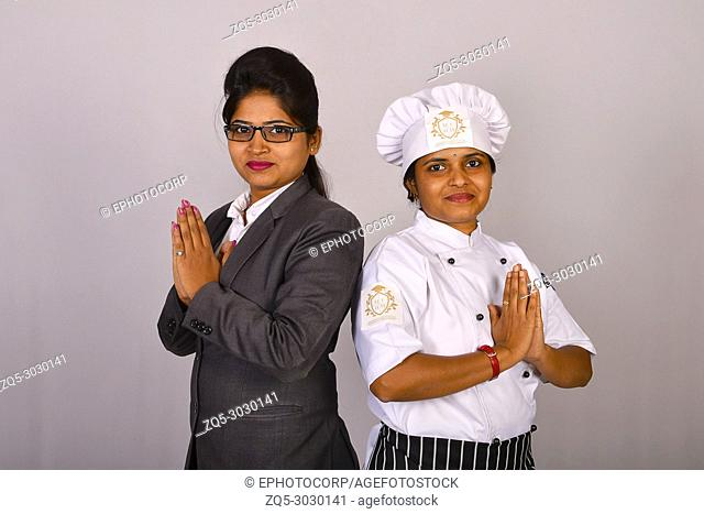 Female chef and staff in a restaurant standing with Namaste greeting