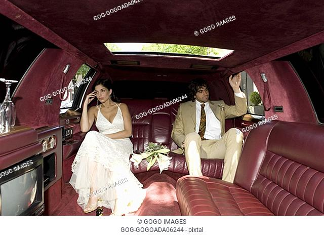Newlywed couple sitting apart in limo
