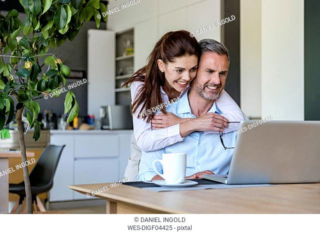 Happy couple at table at home sharing a laptop