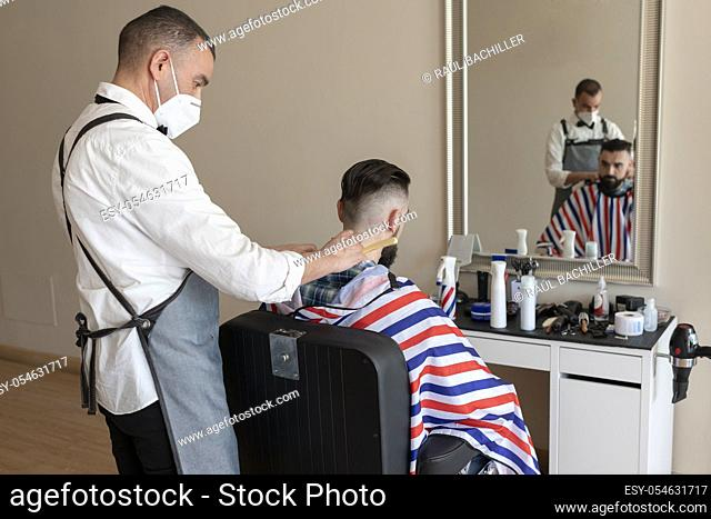 hairdresser grooming beard at barber shop to a client, both wear masks due to the corona virus pandemic