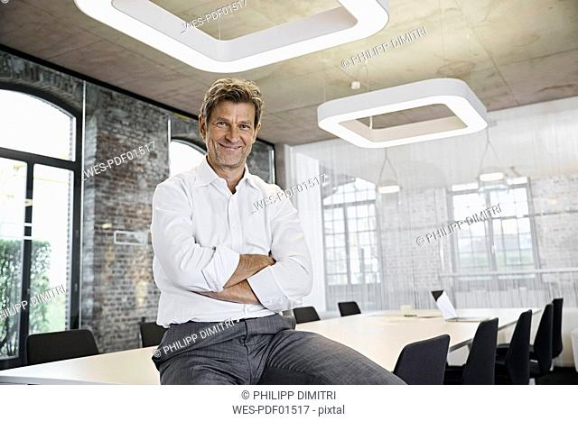 Portrait of confident mature businessman in conference room of modern office