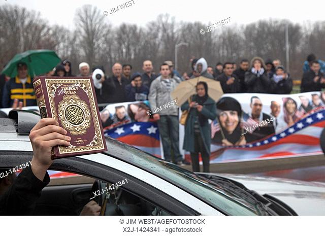 Dearborn, Michigan - A passenger in a passing car holds up a copy of the Quran to cheers from a crowd of mostly young Arab-Americans gathered outside the...