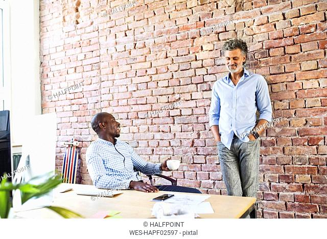 Two smiling colleagues talking in loft office