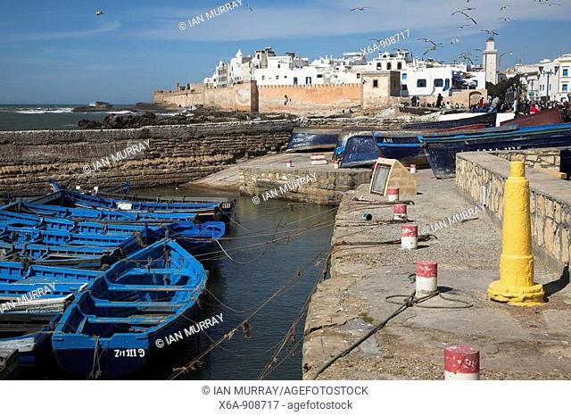 Blue fishing boats and white medina walls from the waterfront, Essaouira, Morocco