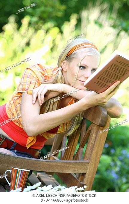 Young blond woman resting in garden reading a book