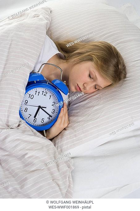 Girl sleeping on bed with alarm clock