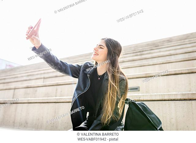 Smiling young woman sitting on stairs taking a selfie