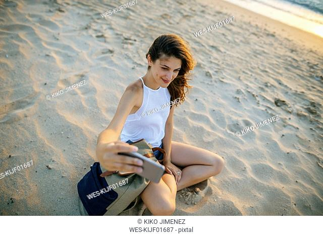 Young woman taking a selfie with a smartphone on the beach