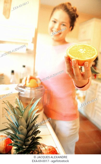 Woman making juice in kitchen