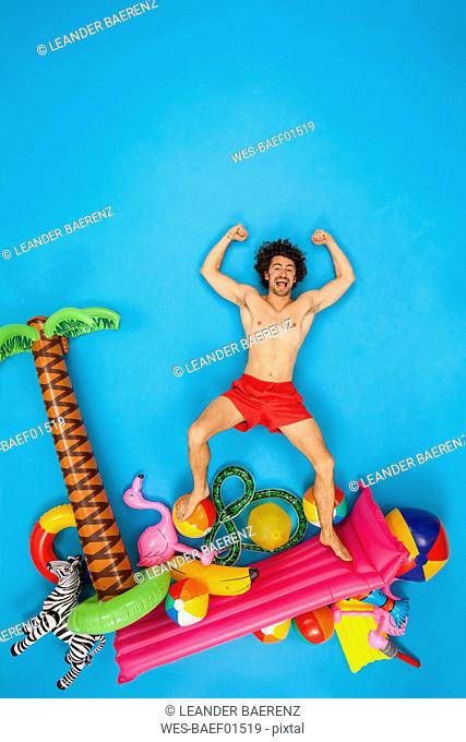 Man having fun on his vacation, flexing muscles