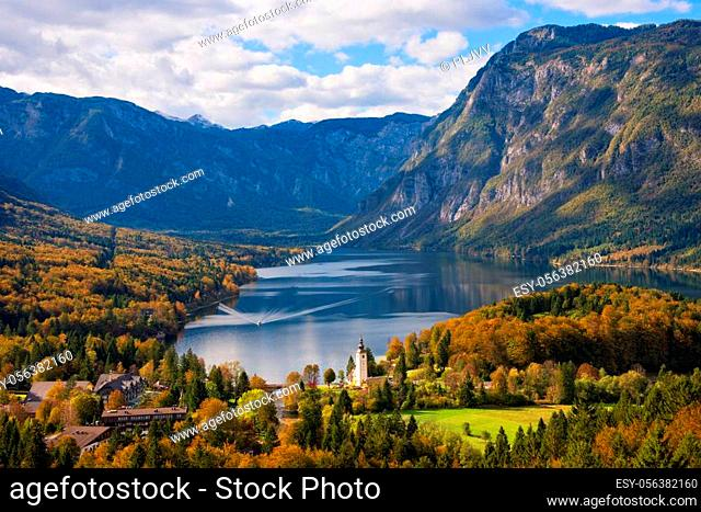 A ferry boat approaching the town of Ribcev Laz with the prominent church at the lakeside of Lake Bohinj surrounded by trees with foliage in autumn colors and...