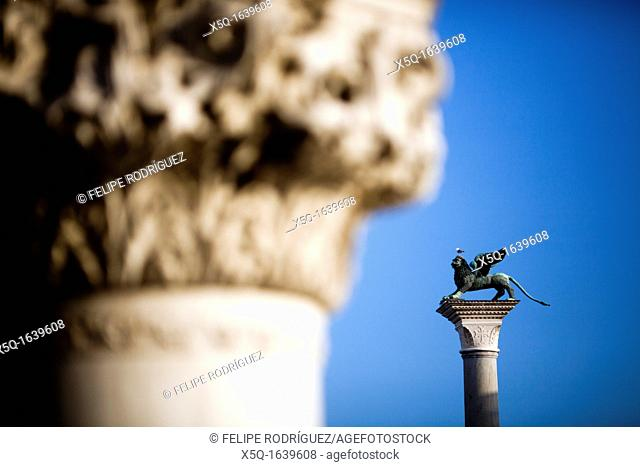 The Piazzetta winged lion background and a column from the Doge's Palace foreground, Venice, Italy