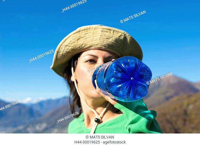 Woman with Hat Drinking Water Fron a Blue Bottle in Switzerland