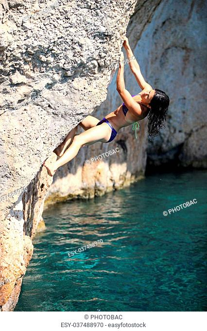 Deep water soloing, young female rock climber on cliff