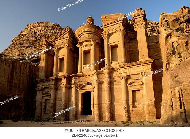 The famous and elaborately carved façade of Al Deir (the Monastery), carved out of a sandstone rock face, 2 men standing on the roof