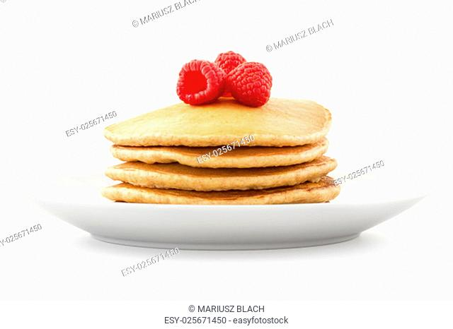 Plate full of pancakes with berries over white background
