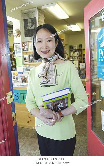 Asian woman carrying book at bookstore