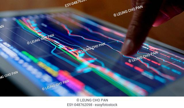 Stock market data on tablet computer at night