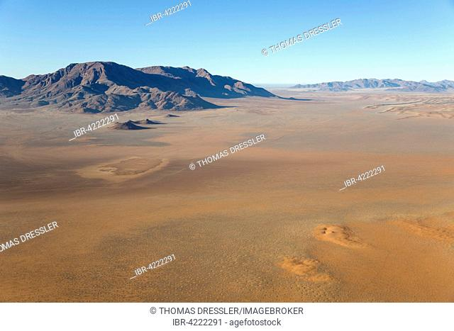 Arid desert plains with so-called Fairy Circles and isolated mountain ridges at the edge of the Namib Desert, aerial view from a hot-air balloon
