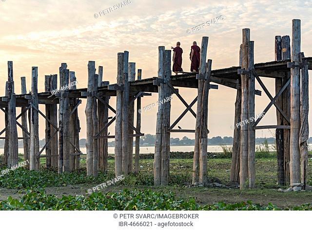 Buddhist monks walking on the U Bein Bridge over Taungthaman Lake, Amarapura, Myanmar