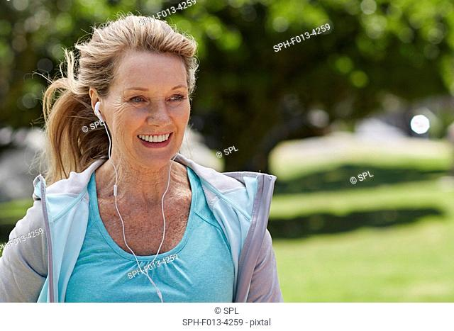 MODEL RELEASED. Senior woman exercising wearing earphones