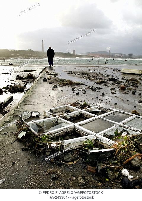 Man walking along the port of San Ciprian, in the coast of Lugo, after heavy windstorm. Galicia, Spain