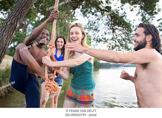 Couples rope swinging above lake