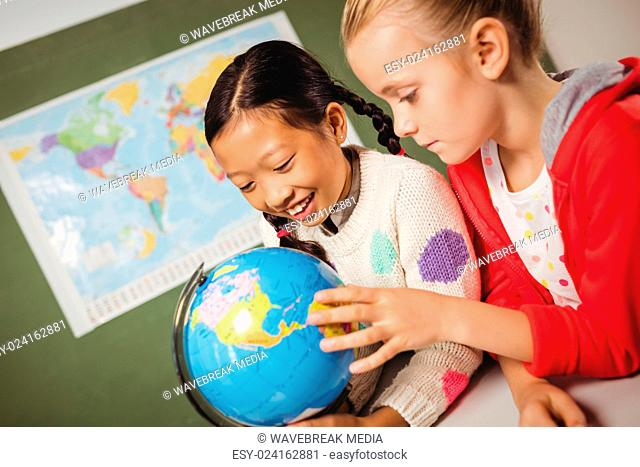 Girls studying the globe