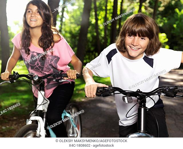 Two happy smiling children riding bicycles in a park, brother and sister, 10 and 13  Active outdoor lifestyle