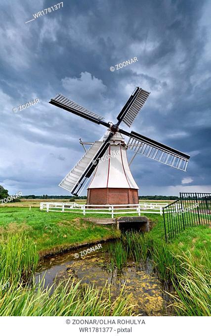 Dutch windmill over clouded sky