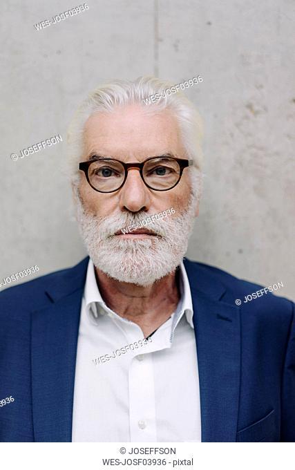 Portrait of serious senior businessman at a concrete wall