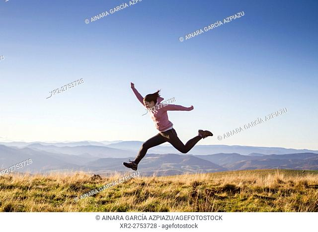 Happy girl jumping on the top of Goñiburu mountain
