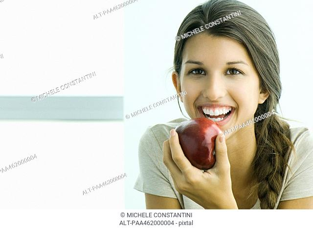 Young female holding apple, smiling at camera, portrait