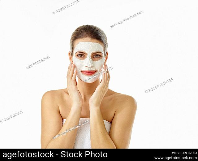 Portrait of smiling woman with beauty mask in front of white background