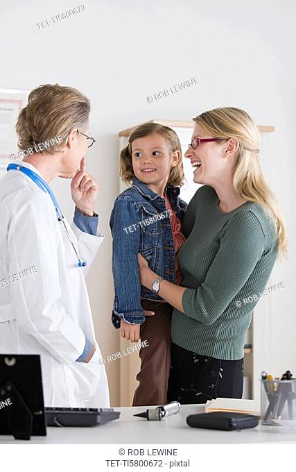 Female doctor talking to small girl 4-5 and her mother