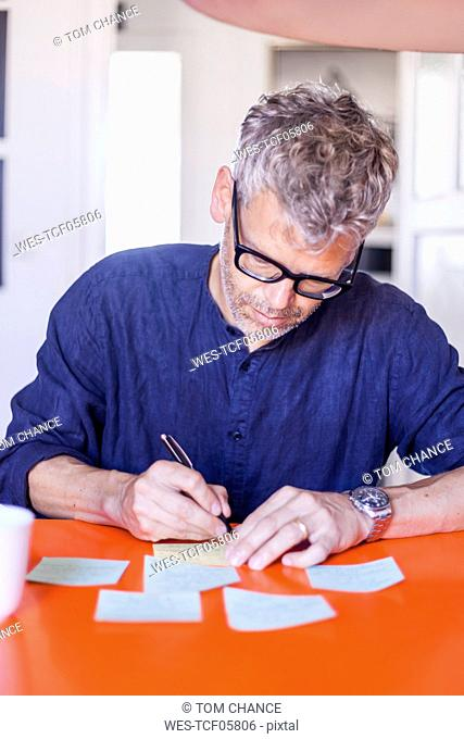 Mature man writing notepads on table at home