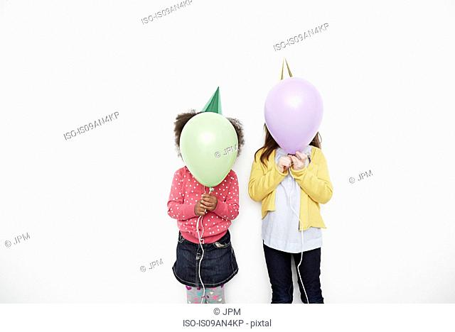 Girls holding balloons in front of face