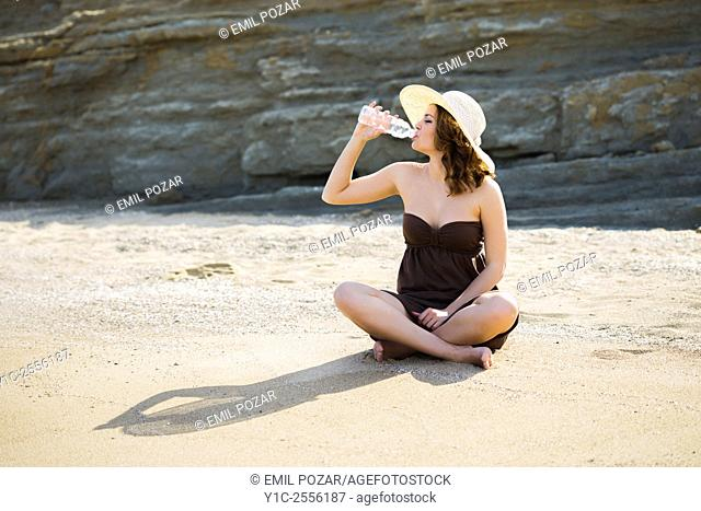 Stock Photo - Drinking water from plastic bottle on beach teenager