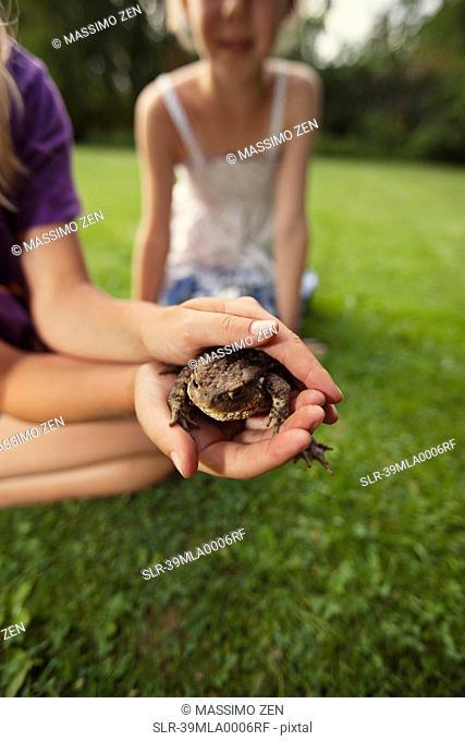 Girl holding frog in backyard