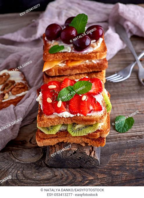 pile of French toast from white bread with cottage cheese, strawberries, kiwi, cherries on a gray wooden board