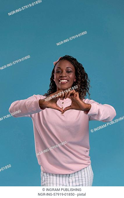 Beautiful young african woman showing heart symbol with fingers on blue background