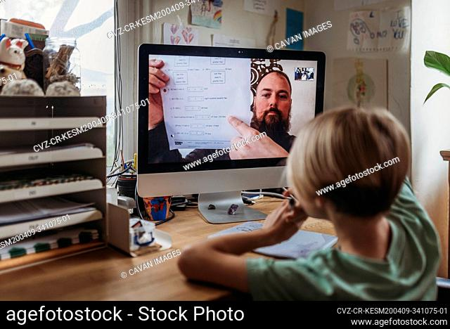 Behind view of school aged boy learning from teacher conducting class